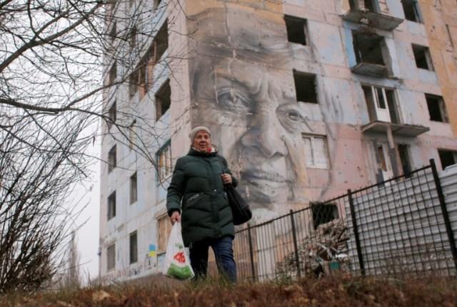 La professeure Maryna Martchenko, près de son portrait peint sur un immeuble d'Avdiivka, le 28 novembre 2019  (AFP - Anatolii STEPANOV)