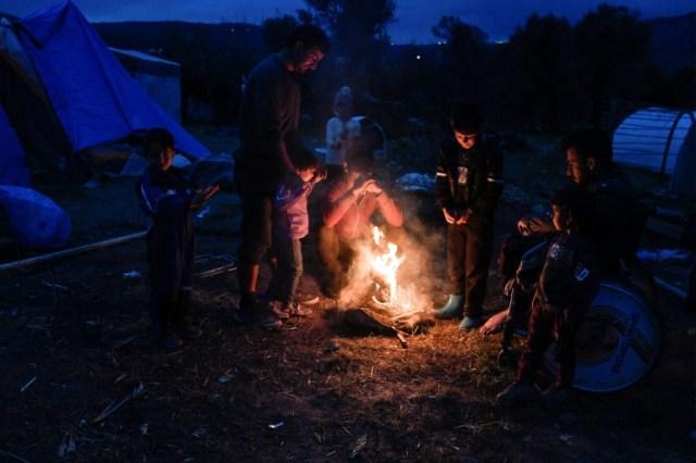 Des migrants kurdes originaires de Syrie allument un feu dans le camp de migrants de l'île de Chios en Grèce, le 11 décembre 2019 (AFP - LOUISA GOULIAMAKI)