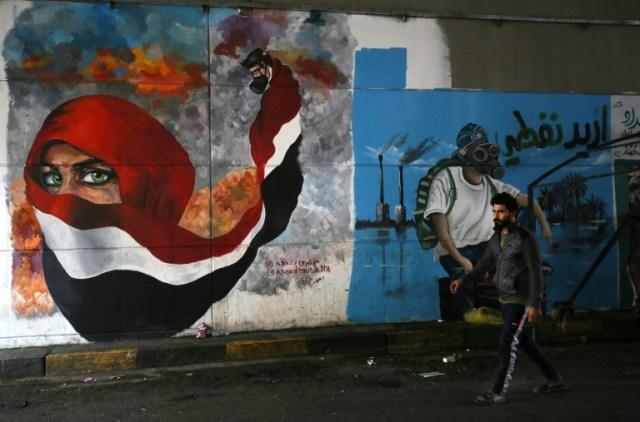 Un Irakien passe devant des peintures murales sur la place de Tahrir, à Bagdad, épicentre de la contestation antigouvernementale, le 13 décembre 2019 (AFP - AHMAD AL-RUBAYE)