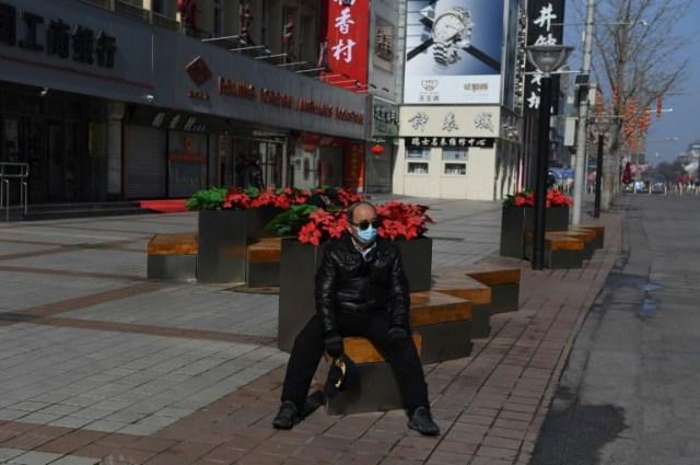 Un homme masquée dans la rue commerçante de Wangfujing à Pékin, désertée en raison du coronavirus, le 10 février 2020 (AFP - GREG BAKER)