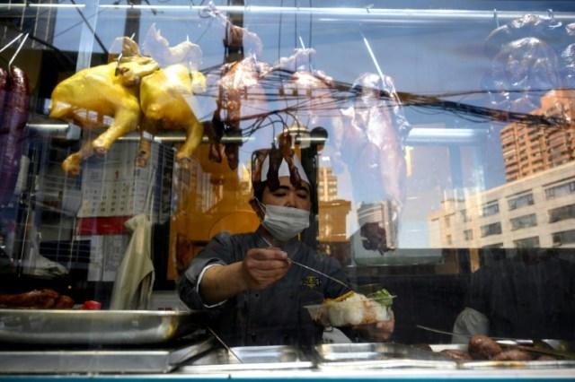 Un cuisinier protégé par un masque dans un restaurant de Shanghai, le 18 février 2020 (AFP - NOEL CELIS)