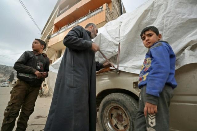 Abou Mohamed et ses enfants couvrent le chargement de leur pick-up, avant de fuir Daret Ezza, dans le nord-ouest de la Syrie, le 18 février 2020 (AFP - Omar HAJ KADOUR)