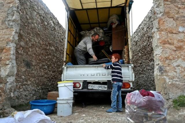 Abou Ahmed et son fils chargent leur voiture avant de fuir Daret Ezza, dans le nord-ouest de la Syrie, le 18 février 2020 (AFP - Omar HAJ KADOUR)