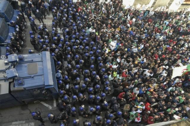 """La police anti-émeutes algérienne bloque la progression de la marche du premier anniversaire du """"Hirak"""" dans la capitale Alger, le 22 février 2020 (AFP - RYAD KRAMDI                        )"""