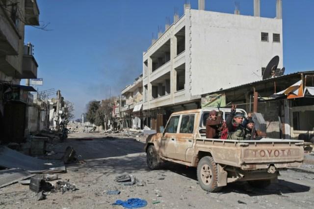Des rebelles à bord d'un pick-up font le V de la victoire dans une rue de la ville de Saraqeb dans la province d'Idleb en Syrie, le 27 février 2020  (AFP - Omar HAJ KADOUR)