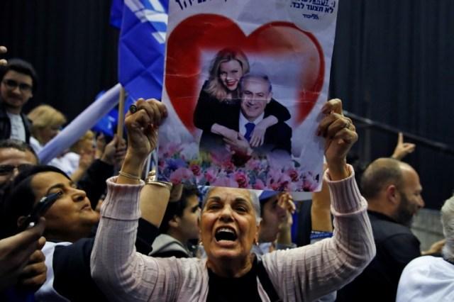 Une partisane du Likoud brandit une photo de Benjamin Netanyahu et de son épouse Sara au QG électoral du parti à Tel Aviv, le 2 mars 2020 (AFP - Jack GUEZ)
