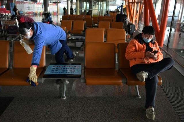 Une employée (G) portant des gants et un masque de protection contre le nouveau coronavirus, désinfecte des sièges à l'aéroport international de Pékin, le 5 mars 2020 (AFP - GREG BAKER)
