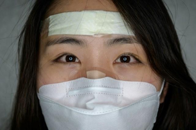 Une infirmière sud-coréenne, Cho Ju-hee, qui s'occupe des malades atteints par le nouveau coronavirus à l'hôpital Dongsan de l'Université Keimyung à Daegu, le 12 mars 2020 (AFP - Ed JONES)