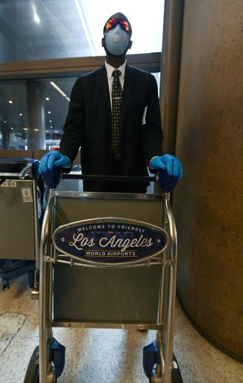 Eugenio Stewart, 46 ans, chauffeur privé attendant un client en provenance de Rome, a enfilé deux paires de gants l'une sur l'autre et porte un masque  (AFP - Robyn Beck)