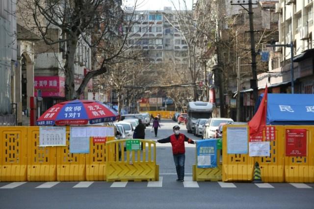 Un homme devant une barrière empêchant l'enrée dans un quartier confiné de Wuhan, le 15 mars 2020 pendant l'épidémie du nouveau coronavirus (AFP - STR)