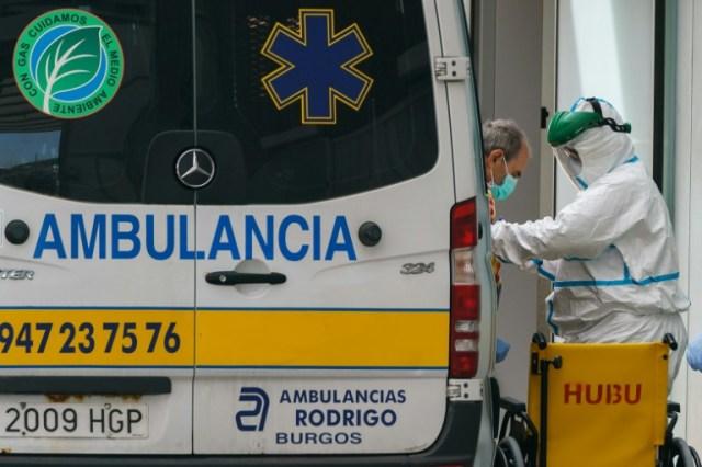 Un membre du personnel soignant aide un homme à descendre d'une ambulance à l'hôpital de Burgos, dans le nord de l'Espagne, le 23 mars 2020 (AFP - CESAR MANSO)