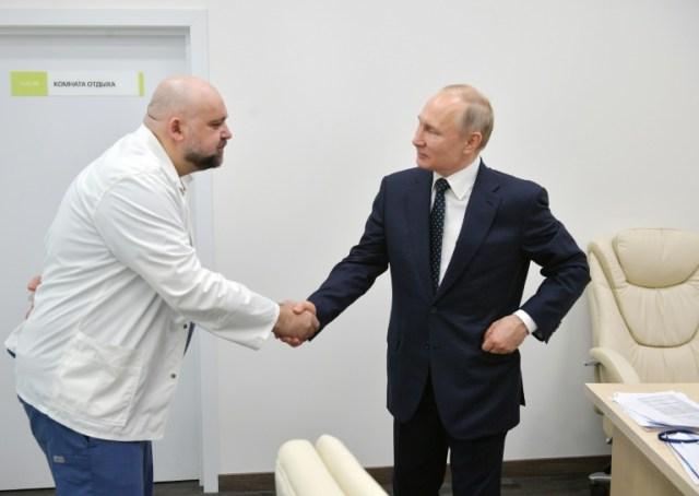 Le président russe Vladimir Poutine serre la main le 24 mars 2020 de Denis Protsenko, responsable de l'hôpital Kommounarka qui traite les malades du Covid-19, et qui s'est révélé contaminé (SPUTNIK/AFP/Archives - Alexey DRUZHININ)