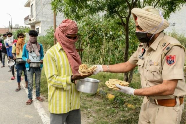 Un policier distribue de la nourriture pendant le confinement à Amritsar (Inde) le 9 avril 2020 (AFP - NARINDER NANU)