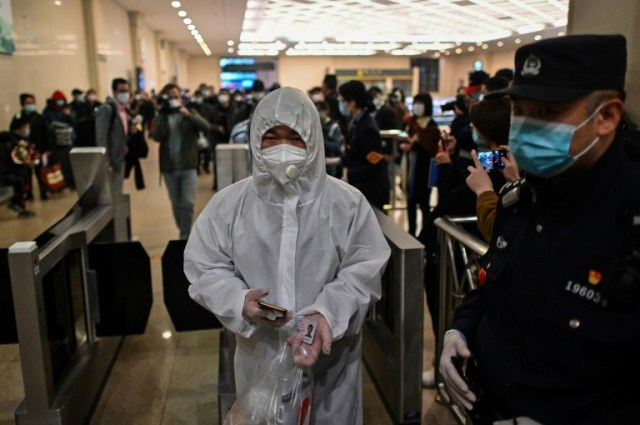 Un homme arrive à la gare de Wuhan pour prendre un des premiers trains pour Pékin le 8 avril 2020 (AFP/Archives - Hector RETAMAL)