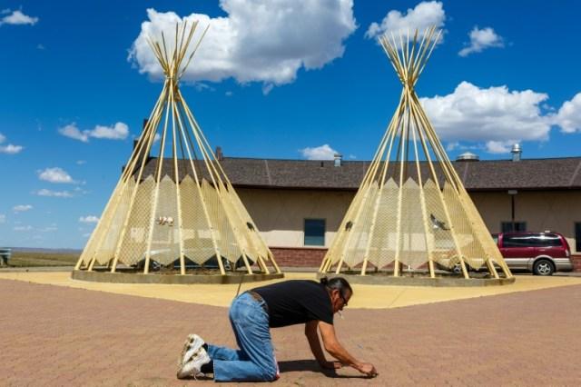 Un homme nettoie le sol devant le centre communautaire de la tribu sioux de Lower Brulé (Dakota du Sud), le 22 avril 2020 (AFP - Kerem Yucel)