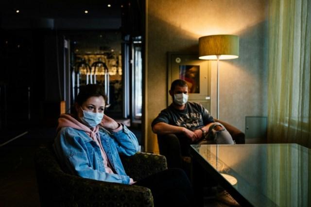 L'infirmière Anastassia Michoustina  (G) et  le médecin Alexeï Manikine (D) se reposent dans le lobby de l'hôtel où ils résident, loin de leurs proches, pendant qu'ils soignent des malades du coronavirus, à Moscou le 29 avril 2020  (AFP - Dimitar DILKOFF)
