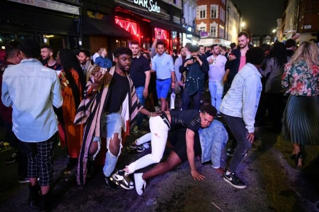Des fêtards dans une rue de Soho, à Londres, après la réouverture des pubs le 4 juillet 2020 (AFP - JUSTIN TALLIS)