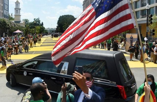 """Des Américains sur la nouvelle place """"Black Lives Matter"""" (les vies des noirs comptent) à Washington regardent passer le convoi funéraire de l'icône de la lutte pour les droits civiques John Lewis le 27 juillet 2020 (AFP - Olivier DOULIERY)"""