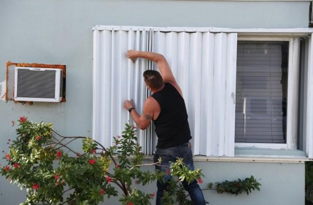 Anthony Perrone barricade sa maison en préparation de l'ouragan Isaias, à Lake Worth, dans le sud de la Floride, le 31 juillet 2020 (GETTY IMAGES NORTH AMERICA/AFP - JOE RAEDLE)