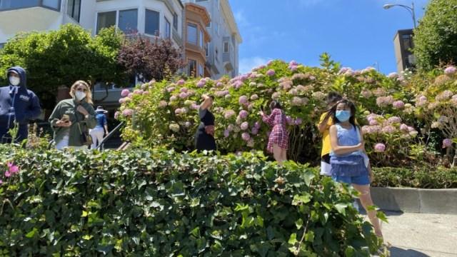 Des touristes portant des masques dans Lombard Street, une des rues les plus célèbres de San Francisco, Etats-Unis,le 2 août 2020 (AFP - Daniel SLIM)