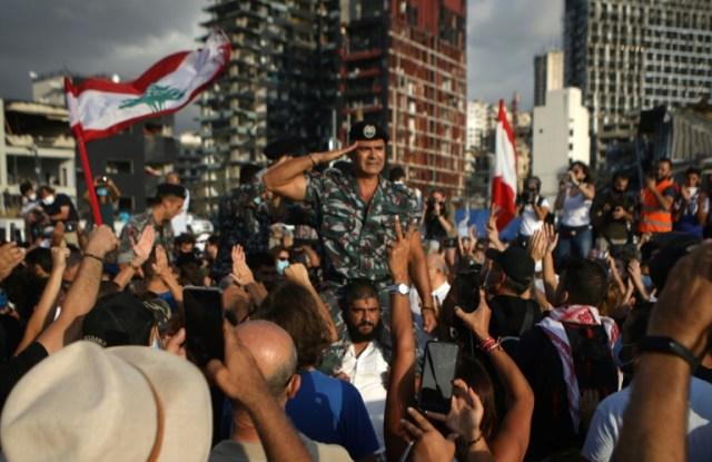 La foule acclame les forces de la Défense civile libanaise lors d'une cérémonie en hommage aux victimes de l'explosion, le 11 août 2020 à Beyrouth (AFP - PATRICK BAZ)