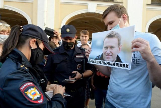 Des policiers, à St-Pétersbourg le 20 août 2020, vérifient les papiers d'un homme venu manifester son soutien à l'opposant Alexeï Navalny, hospitalisé d'urgence après ce que ses proches dénoncent comme un empoisonnement (AFP - OLGA MALTSEVA)