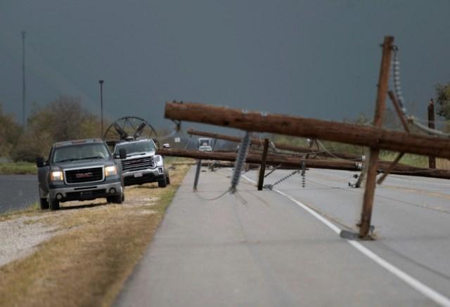 Des poteaux électriques couchés sur une route à Cameron, au sud de Lake Charles, après le passage de l'ouragan Laura, le 28 août 2020 en Louisiane (AFP - ANDREW CABALLERO-REYNOLDS)