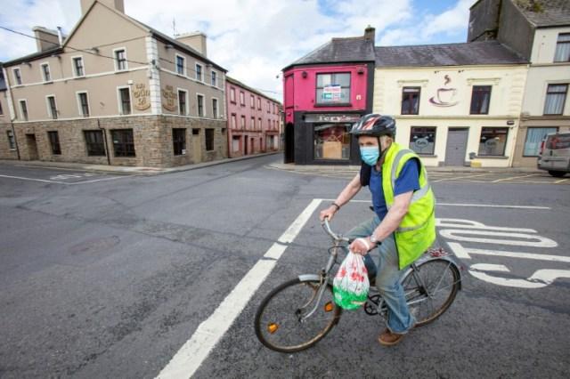 """Un homme à vélo portant un masque devant le """"Tery's bar"""", fermé à cause de la pandémie de coronavirus, dans le village de Dunmore, dans l'ouest de l'Irlande, le 3 septembre 2020  (AFP - PAUL FAITH)"""