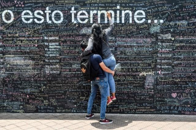 Une femme écrit sur le Mur de l'espoir, le 26 octobre 2020 à Lima, au Pérou (AFP - ERNESTO BENAVIDES)