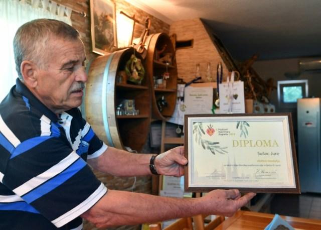 Jure Susac montre la récompense qu'il a obtenue pour son huile d'olive, le 19 octobre 2020 près de Ljubuski, en Bosnie (AFP - ELVIS BARUKCIC)