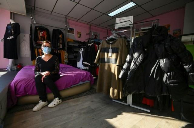 Véronique Weingarten, en grève de la faim, a installé un lit dans la vitrine de sa boutique de prêt-à-porter, le 31 octobre 2020 à Blotzheim, dans le Haut-Rhin (AFP - SEBASTIEN BOZON)