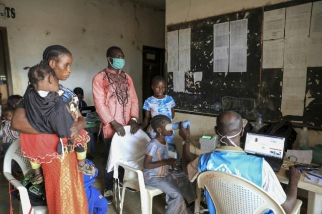 Une équipe du HCR enregistre les données biométriques d'une jeune réfugiée centrafricaine, à Garoua-Boulaï, au Cameroun, le 8 janvier 2021. (AFP - Daniel Beloumou Olomo)