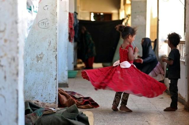 Des enfants jouent dans une école qui abrite des Yéménites déplacés par les combats entre les rebelles Houthis et une coalition menée par l'Arabie saoudite, dans la ville d'al-Tourba (AFP/Archives - AHMAD AL-BASHA)