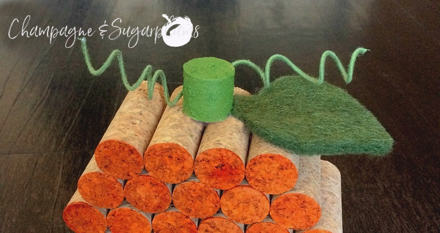 Cork stem, wire vine and felt leaf being added to pumpkin by Champagne and Sugarplums