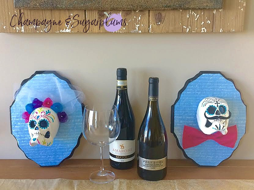 Day of the Dead Crafts and Activities for Kids featured by top Seattle lifestyle blogger, Marcie in Mommyland: Sugar skulls on a table with wine bottles and glasses by Champagne and Sugarplums