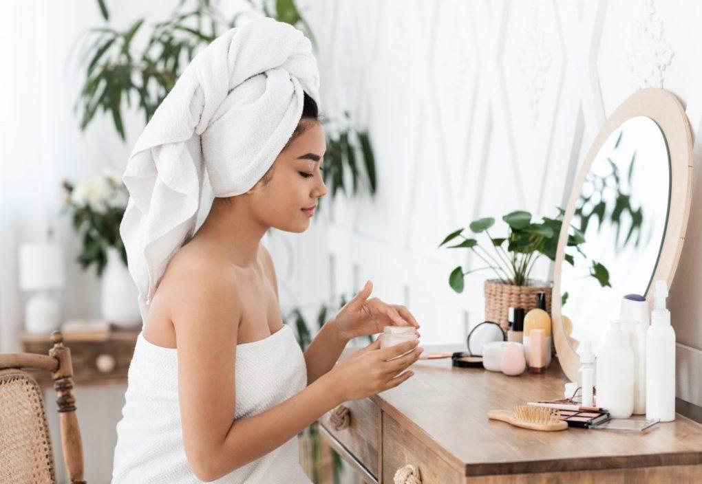 30 something year old Woman applying skincare