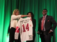 Microsoft Canada president Janet Kennedy presents a jersey to Canadian partner of the year Cloud IT at the 2014 Impact Awards.