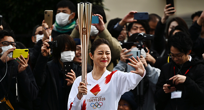 Japanese actress Satomi Ishihara waves while holding an Olympic torch during a rehearsal of the Tokyo 2020 Olympics torch relay in Tokyo on February 15, 2020. CHARLY TRIBALLEAU / AFP
