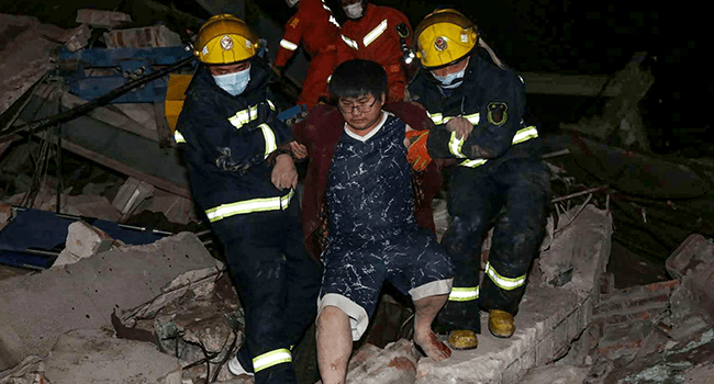 A man is helped out of the rubble of a collapsed hotel by rescuers in Quanzhou, in China's eastern Fujian province on March 7, 2020. STR / AFP