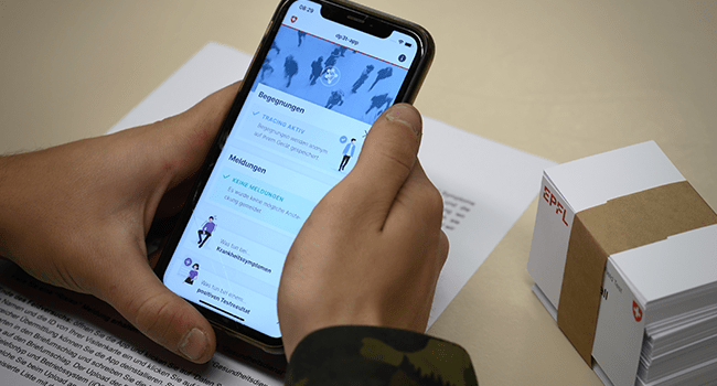 A Swiss soldiers holds his smartphone showing an app, created by the Swiss Federal Institute of Technology Lausanne (EPFL) that could help trace those who have been in close contact with someone who tested positive for the COVID-19. Fabrice COFFRINI / AFP