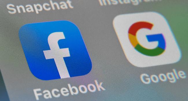 This file illustration taken on October 1, 2019 shows the logos of mobile apps Facebook and Google displayed on a tablet in Lille, France. DENIS CHARLET / AFP