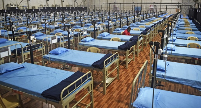 A man sits next to beds at a newly built hospital to treat Covid-19 coronavirus patients at the Mahalaxmi Racecourse, in Mumbai on July 7, 2020. - India on July 6 became the country with the third-highest coronavirus caseload in the world, as a group of scientists said there was now overwhelming evidence that the disease can be airborne -- and for far longer than originally thought. India's major cities including New Delhi and Mumbai are suffering the most, and critics say not enough tests are being conducted -- meaning that many COVID-19 infections are likely to go undiagnosed. (Photo by Punit PARANJPE / AFP)