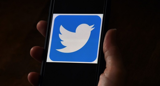 """(FILES) In this file photo illustration, a Twitter logo is displayed on a mobile phone on May 27, 2020, in Arlington, Virginia. - Twitter shares closed the formal trading day up more than 7 percent after word spread of a team codenamed """"Gryphon"""" working on a subscription platform. (Photo by Olivier DOULIERY / AFP)"""
