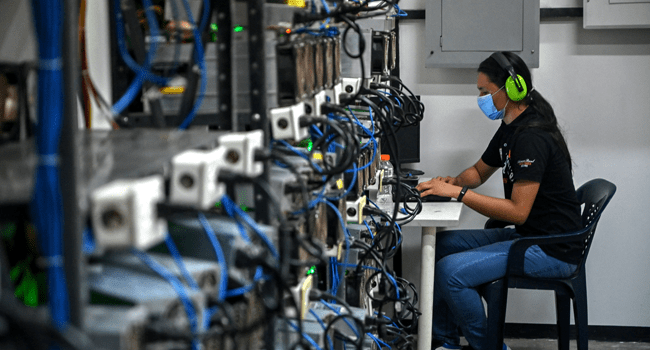 An employee inspects computers used to mine Bitcoins at the mining showroom of the Doctorminer company in Caracas on August 18, 2021. Federico PARRA / AFP
