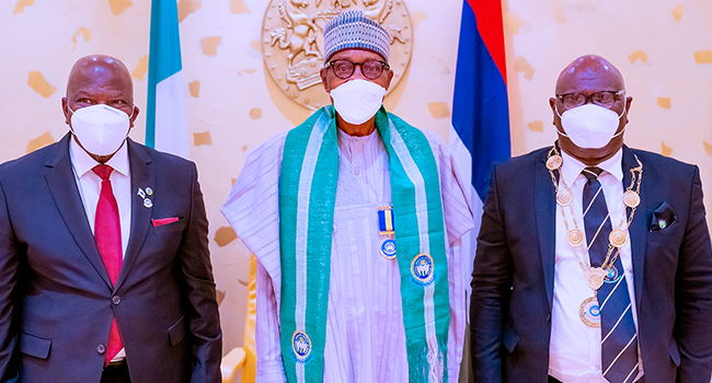 President Muhammadu Buhari is flanked by CIIN President Sir Muftau Oyegunle (R) and Commissioner for Insurance Mr. Sunday Thomas (L) as he receives in courtesy visit the Governing Council of the Chartered Insurance Institute of Nigeria (CIIN) in State House on October 14, 2021. Bayo Omoboriowo/State House