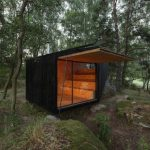 A Small Retreat House Built in the Forest on a Giant Boulder