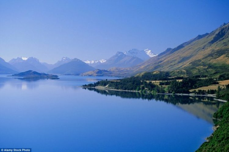 The still Lake Wakatipu at Glenorchy appears to merge into the blue-hued Mount Earnslaw behind
