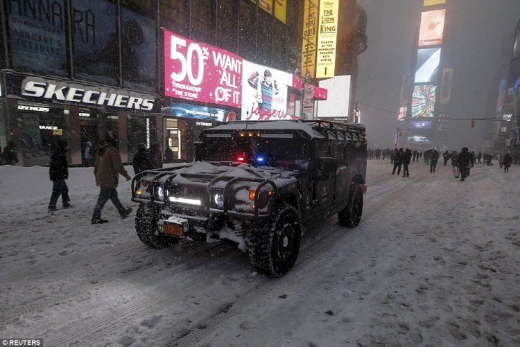 A U.S. Army SUV makes its way down 7th Avenue during the snowstorm in Times Square in the Manhattan borough of New York