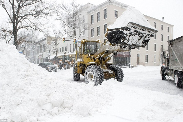 A digger loads snow into a dumper truck in Alexandria, Virginia, on Saturday amid heavy snowfall which caused traffic accidents across the state