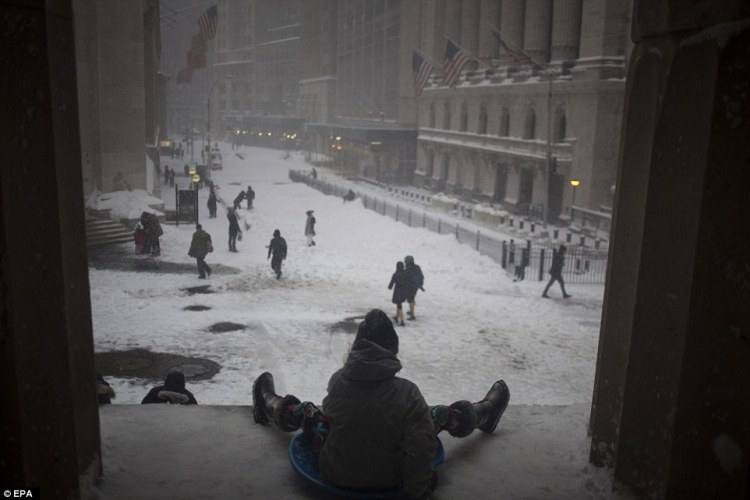 A group of kids slide down a hill in the snow near the New York Stock Exchange (NYSE) in Lower Manhattan, New York on Saturday